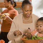 MyBenefits - Grandmother, mother and granddaughter preparing dinner together.